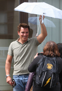 Post a picture of an actor holding an umbrella.