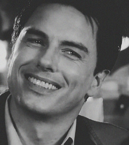 Post a picture of an actor with a cute smile in black and white.