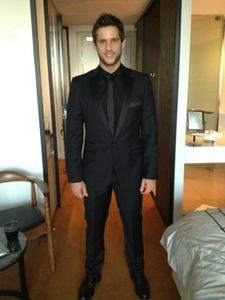 Post a picture of an actor wearing a black suit.