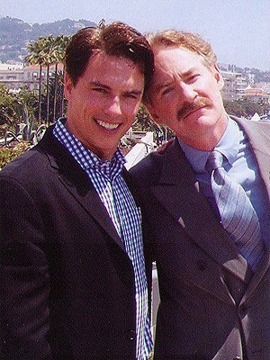 Post a picture of an actor with someone with a mustache.