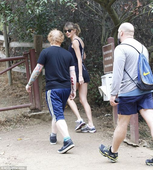 Three's a crowd: The country singer's bodyguard carried a small backpack as she chatted with Sheeran