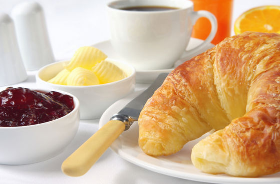 A Of Croissants, Coffee And Butter/Jelly Served With Breakfast