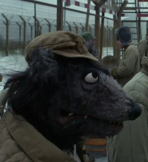 Black Dog, whose awali movie appearance was in 2005's Muppets Wizard of Oz as a flying monkey, pictured here, is a gulag prisoner this time around.