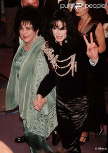 Michael escorting Elizabeth Taylor to her birthday party back in 1997