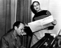 Brando rehearsing for Guys and Dolls, with the show's songwriter, Frank Loesser, at the piano.