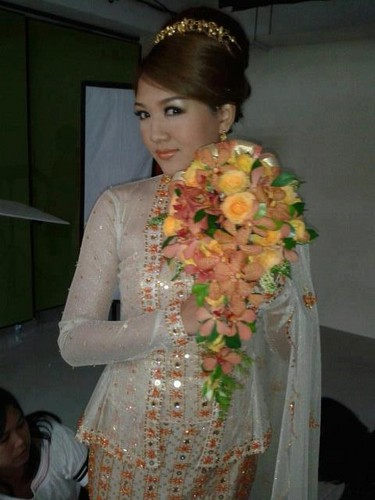 Thet Mon Myint Hintergrund probably with a bridesmaid and a bouquet called TMM traditional wedding dress CF