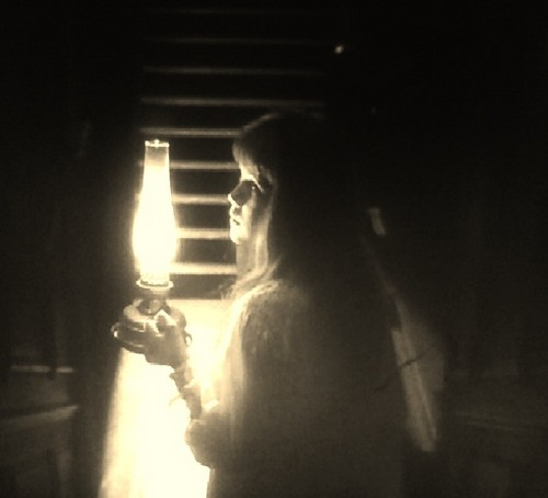 Mary walking down a dark staircase at night