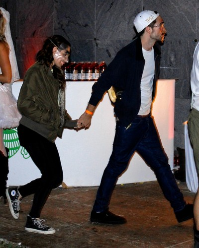 Rob & Kristen holding hands at a Halloween party [Oct 31]
