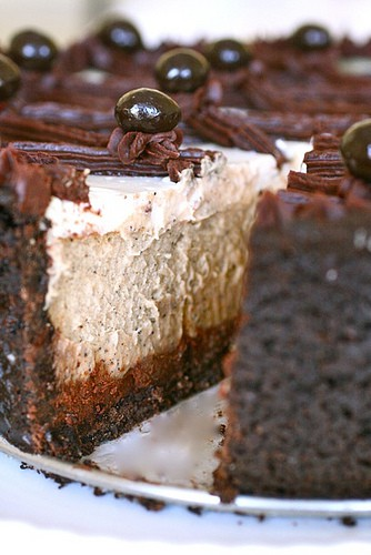 Chocolate wallpaper with a frosted layer cake titled chocolate fudge cheesecake