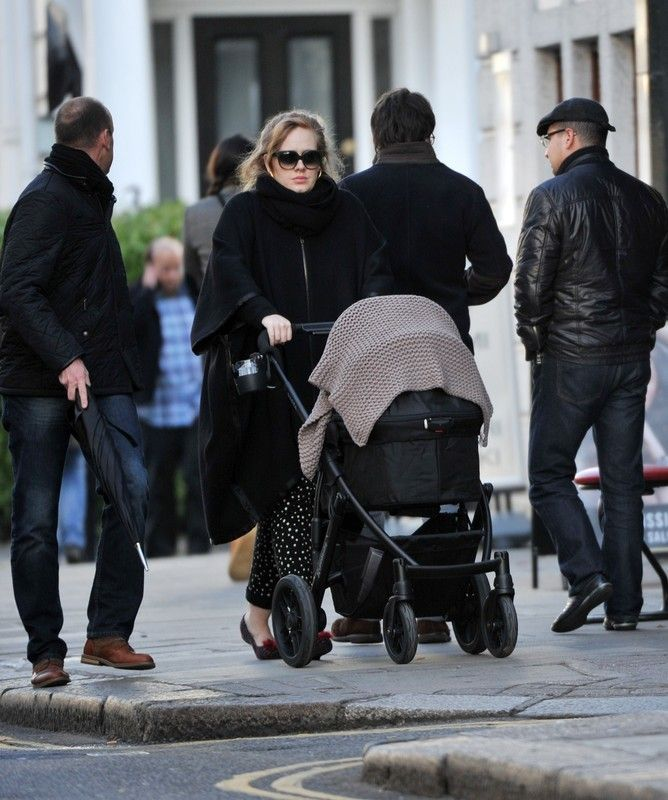 Adele walking with his son through the streets of London