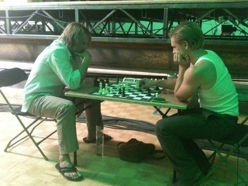 Josh Hutcherson and Woody Harrelson playing chess on set