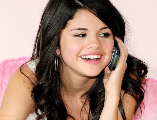 瑟琳娜·戈麦斯 壁纸 probably with a cellular telephone and a portrait called Selena Gomez