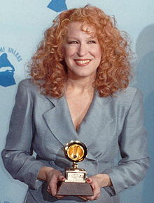 The 90s wallpaper probably with a business suit and a well dressed person entitled Bette Midler