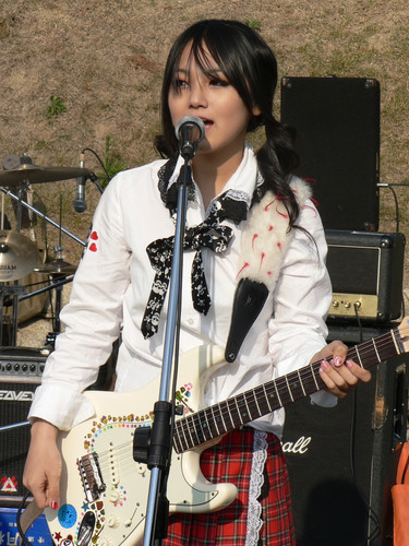 SCANDAL achtergrond with a guitarist and a concert entitled 日本女の子バンドのスキャンダル 笹崎 まみ