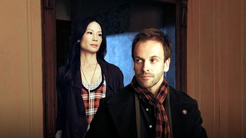 Sherlock & Joan karatasi la kupamba ukuta with a well dressed person and a business suit called Sherlock and Joan