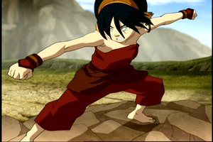 toph riding on a rock