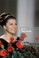 next to a bunch of long stem red roses in her villa in the Appia Antica. Rome (Italy), 1964