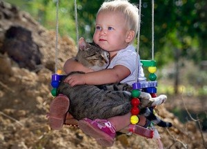 Baby Playing With A Cat While On The Swing