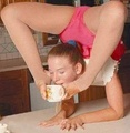 Contortionist drinking a cup of water using her feet