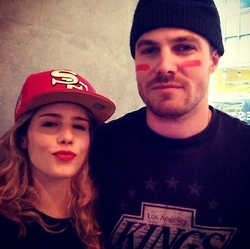 Stephen Amell & Emily Bett Rickards wallpaper probably with a berretto, tappo and a ski berretto, tappo called Stephen Amell Emily Bett Rickards