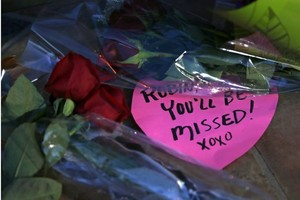 A heart-shaped note and several bouquets of bunga lay in front of the halaman awal of Robin Williams