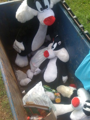 large Sylvester cat plush toys in my poubelle, benne à ordures with cuisine trash, spoiled food, and dog feces