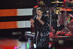 Nick Jonas performs in the rain on stage during the 2014 엠티비 EMA Kick Off at the Klipsch Amphitheate