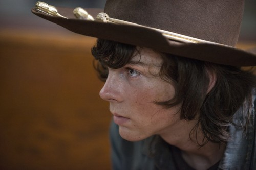 Chandler Riggs Hintergrund with a snap brim hat, a campaign hat, and a fedora called Carl Grimes