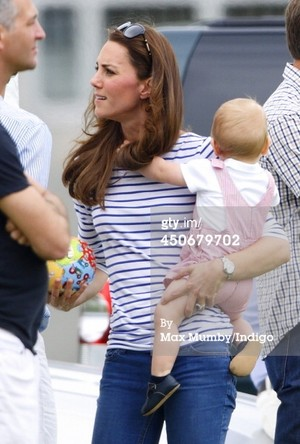 Prince George of Cambridge plays with a football whilst holding his mother Catherine