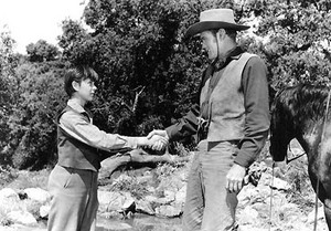 Tommy Kirk as Travis Coates and Chuck Connors as Burn Sanderson in Old Yeller