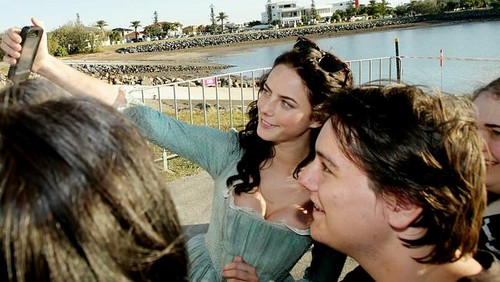 Kaya Scodelario achtergrond probably with a business district and a straat titled Pirates Of The Caribbean: Dead Men Tell No Tales