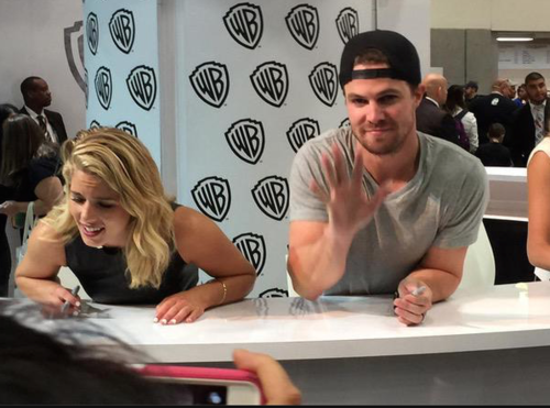 Stephen Amell & Emily Bett Rickards wallpaper possibly with a sign called Stephen Amell and Emily Bett Rickards signing autographs at SDCC 2015.
