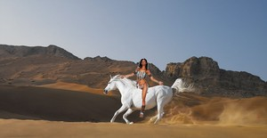 a native american woman riding on her beautiful white steed
