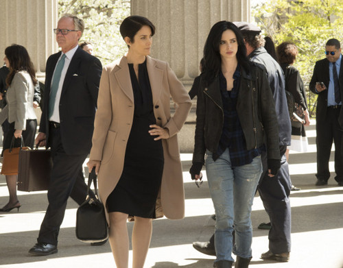 Netflix achtergrond with a business suit and a well dressed person entitled First foto's of Marvel's 'Jessica Jones'