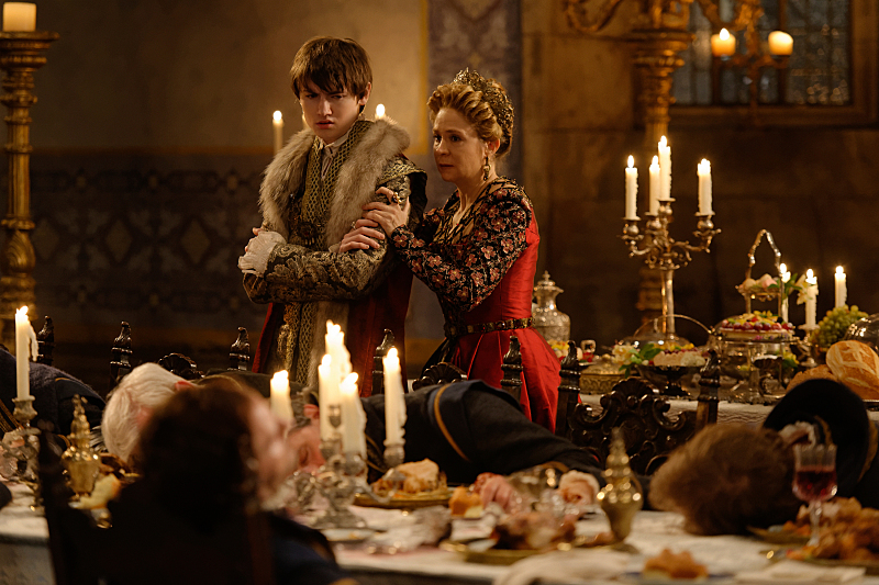 """King Charles and Catherine hold each other while people are poisoned around them in Reign's """"To the Death""""."""