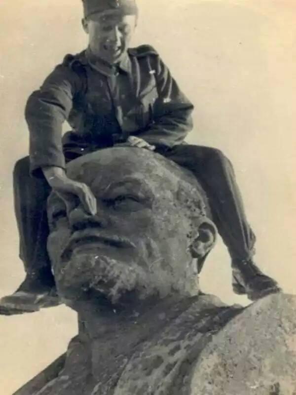 soldier squeezing Lenin's statue nose