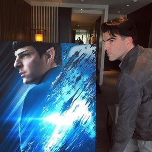 Zachary Quinto posing inayofuata to a poster of Spock