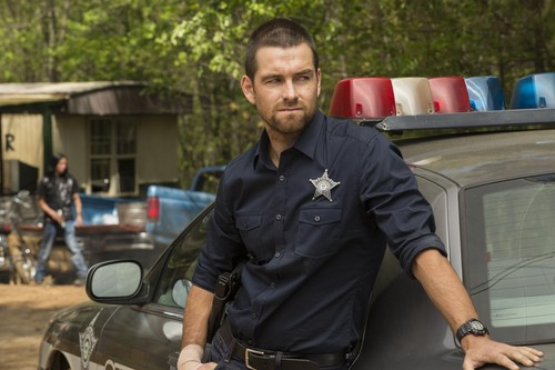 Antony Starr achtergrond with a business suit, a green beret, and a straat called Antony Starr as Lucas kap in 'Banshee'