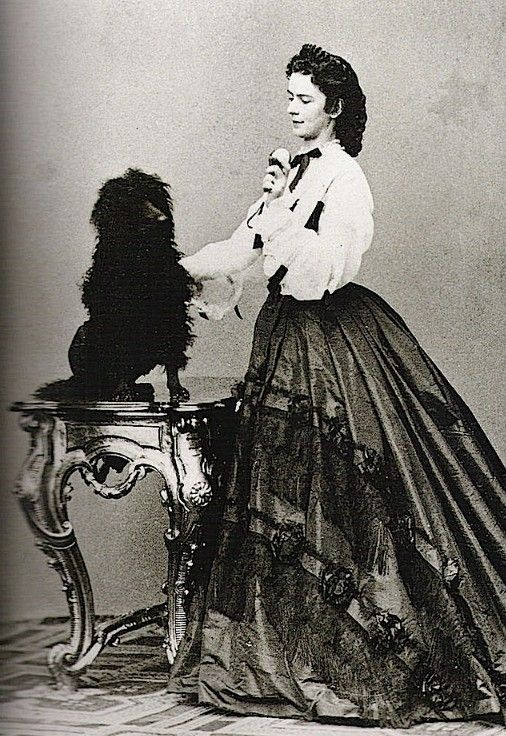 Empress Elizabeth  in 1864  playing with a dog