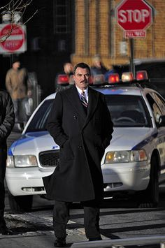 Frank Reagan in Front of a Policecar