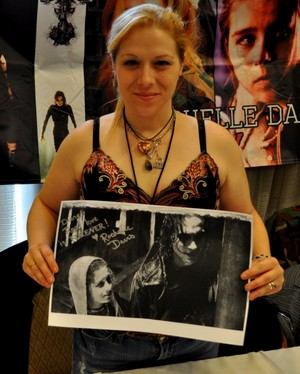Rochelle Davis holding a picture of herself and Brandon Lee