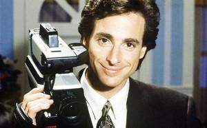 Bob Saget holding a ビデオカメラ