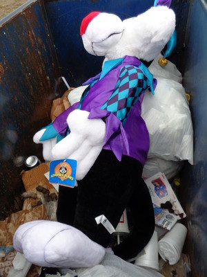 large plush jester Sylvester in the trash with dog feces in the rain