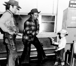 Clint Eastwood and Eric Fleming have a quick draw contest with a young child on the set of Rawhide (