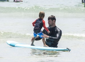 Chris teaching one of his sons how to surf