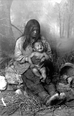 Mescalero Apache Woman Holding Infant Cradleboard Nearby - Randall - 1888