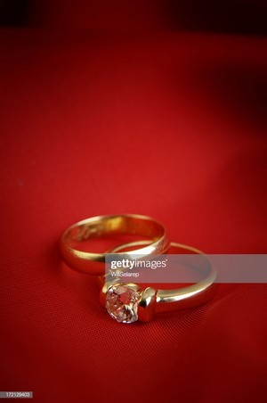 Two vàng Rings In Front Of Red Background
