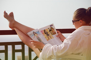 She reading a Cosmoroltan Magazine