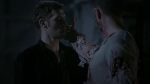 Why is Klaus looking at this man's tattoo?