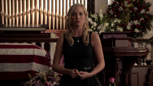 What does Caroline do at the end of her mom's funeral?